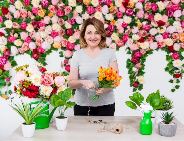 꽃집에서 일하는 웃는 성숙한 여성 꽃집 또는 정원사의 초상화