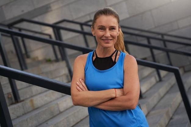 街でトレーニングした後、屋外でポーズをとってスポーツウェアの成熟した女性の笑顔の肖像画