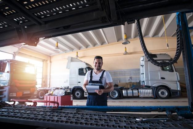 Портрет улыбающегося механика, стоящего в мастерской по ремонту грузовиков.