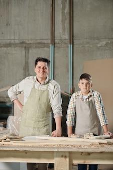 ワークショップで木片とテーブルに立っているエプロンで笑顔の中年大工と彼の10代の息子の肖像画