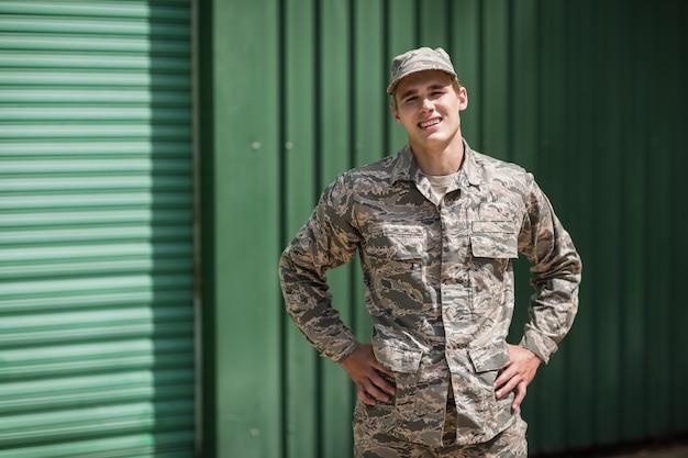 Портрет улыбающегося военного солдата, стоящего с руками на бедре в учебном лагере