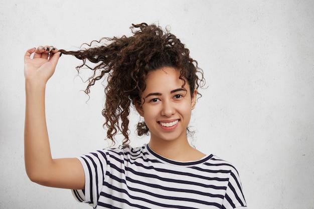 Портрет улыбающейся женщины смешанной расы держит руку на хрустящем замке, носит повседневную полосатую футболку, я