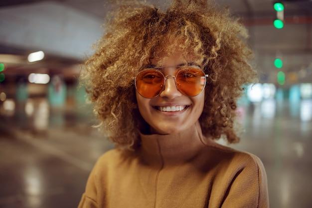 Портрет улыбающейся хип-хоп девушки смешанной расы с солнцезащитными очками, глядя на камеру.