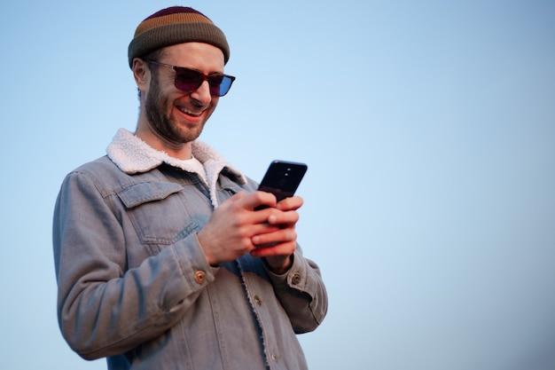 푸른 하늘의 배경에 손에 스마트 폰으로 웃는 현대 남자의 초상화