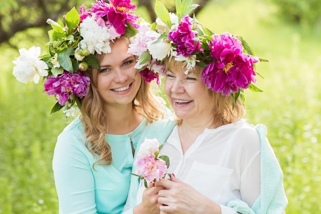 笑顔の母と娘のポーズと屋外の花の花輪でハグの肖像画。家族の概念。母と娘の関係。