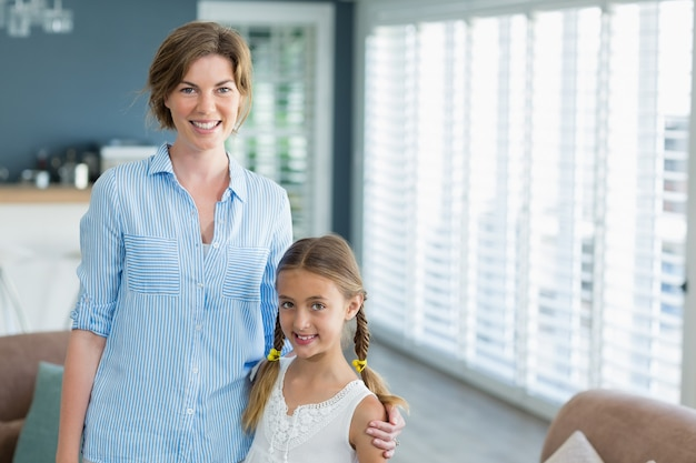 Портрет улыбающейся матери и дочери, стоя вместе в гостиной