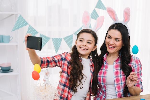 휴대 전화에 셀카를 복용하는 머리에 토끼 귀로 웃는 어머니와 딸의 초상화