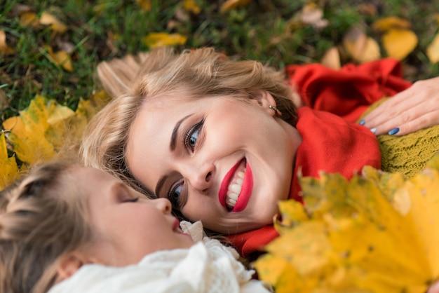 Портрет улыбающейся матери и дочери с листьями в руках, лежащих на желтой траве