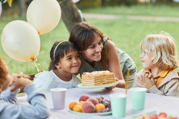 屋外での誕生日パーティー中にかわいい女の子にバースデーケーキを持って笑顔の母親の肖像画