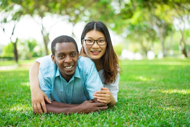 公園の草の上に横たわっている笑顔の多民族カップルの肖像