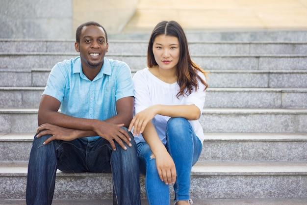 階段に座っている笑顔の多民族学生の肖像画。