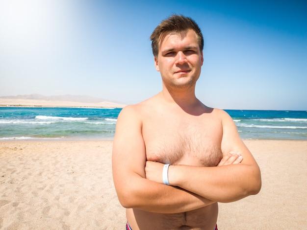 바다와 푸른 하늘에 대 한 해변에서 포즈 웃는 근육 질의 젊은 남자의 초상화