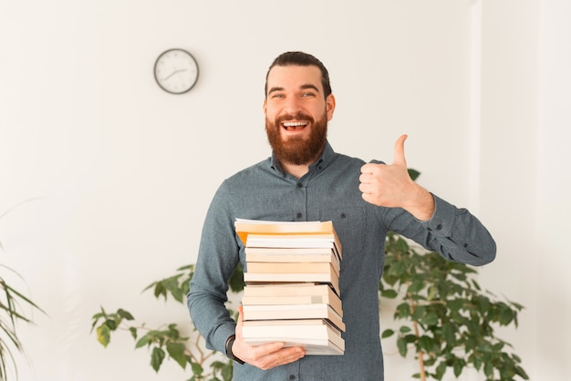 많은 책을 들고 엄지 손가락을 보여주는 웃는 회사원의 초상화