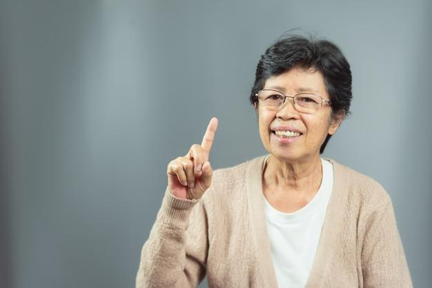 Портрет улыбающегося старуха, думая идеи на сером