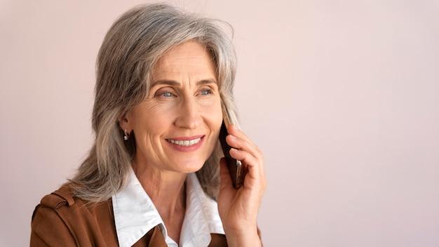 Портрет улыбающейся пожилой женщины, разговаривающей по телефону