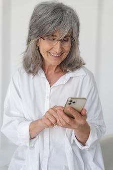 집에서 휴대폰으로 웃고 있는 노부인의 초상화