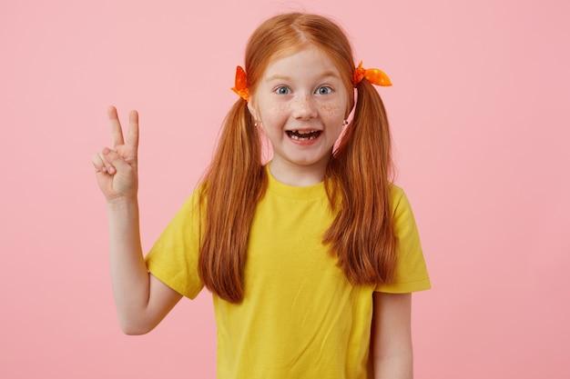 Портрет улыбающейся рыжеволосой девушки с миниатюрными веснушками с двумя хвостами, смотрит и показывает жест мира, носит желтую футболку, стоит на розовом фоне.