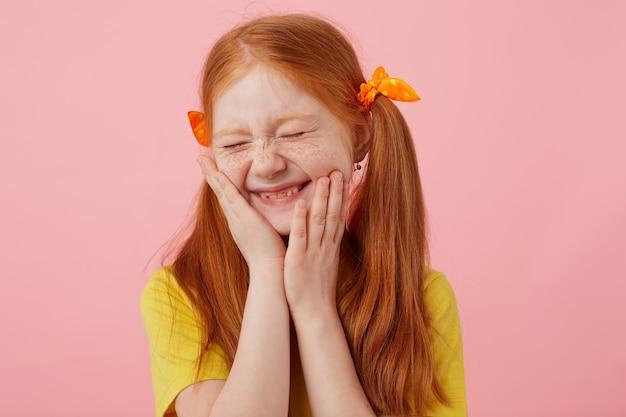 Портрет улыбающейся рыжеволосой девушки с миниатюрными веснушками с двумя хвостами, с закрытыми глазами трогает щеки, носит желтую футболку, стоит на розовом фоне.