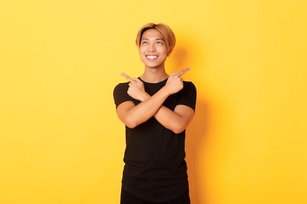 Портрет улыбающегося довольного азиатского парня, смотрящего влево и принимающего решение, указывающего в сторону, желтая стена