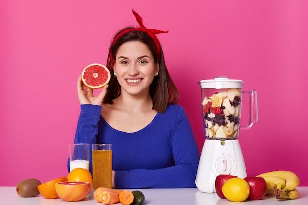 肯定的な女性の持株を笑顔の肖像画は彼女の手で果物をカットしました。若いモデルはスムージーの準備ができるのを待ちます。陽気な幸せな女は喜んで健康的な食事に固執します。健康的なライフスタイルのコンセプトです。