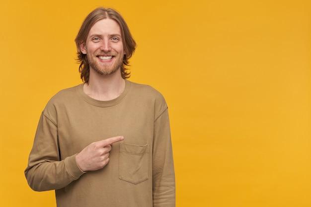 금발 헤어 스타일과 수염을 가진 미소, 긍정적 인 남성의 초상화. 베이지 색 스웨터를 입고. 노란색 벽 위에 고립 된 복사 공간에서 오른쪽으로 손가락을 가리키는