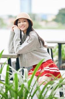 屋外のテーブルに座って笑顔のポジティブな若いアジアの女の子の肖像画