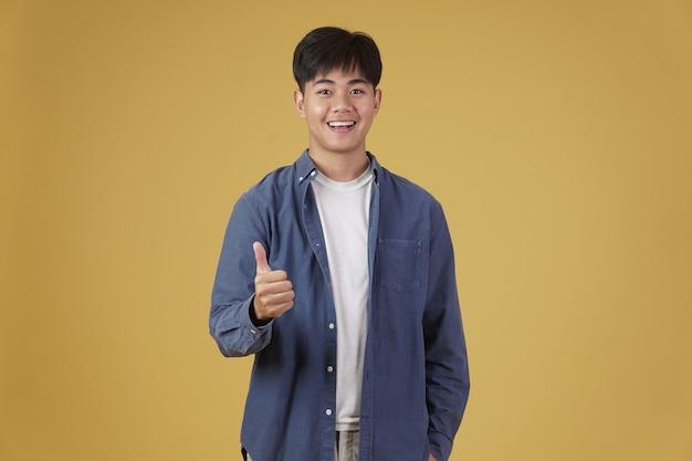 웃는 긍정적 인 젊은 아시아 남자의 초상화는 고립 된 표현을 승인하는 제스처를 엄지 손가락으로 부담없이 옷을 입고