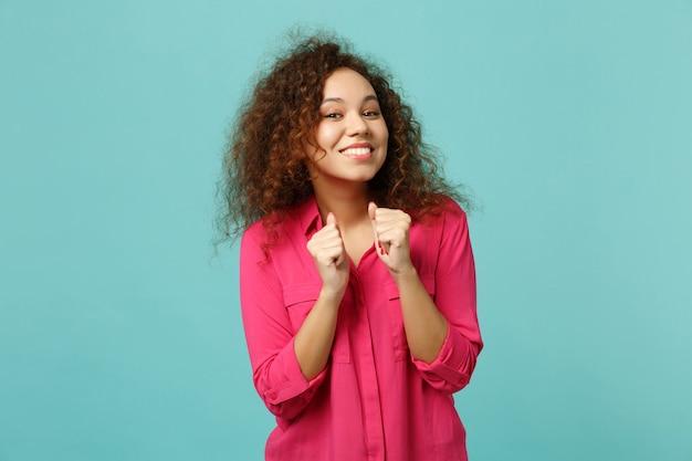 スタジオで青いターコイズブルーの壁の背景に分離された拳を握りしめるピンクのカジュアルな服を着て笑顔のかわいいアフリカの女の子の肖像画。人々の誠実な感情、ライフスタイルのコンセプト。コピースペースをモックアップします。