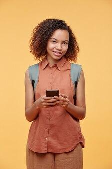 スマートフォン、スタジオショットを使用してソーシャルメディアで通信するカジュアルな服装で笑顔のかわいいアフリカ系アメリカ人の学生の女の子の肖像画