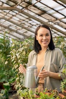 Портрет улыбающейся красивой азиатской женщины, стоящей с лейкой среди тепличных растений