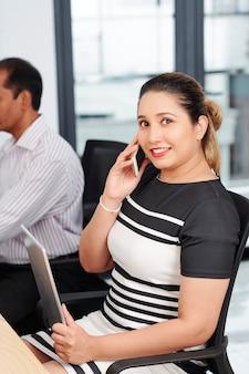 オフィスの机に座って電話で話している手にタブレットコンピューターと笑顔のかわいいビジネス女性の肖像画