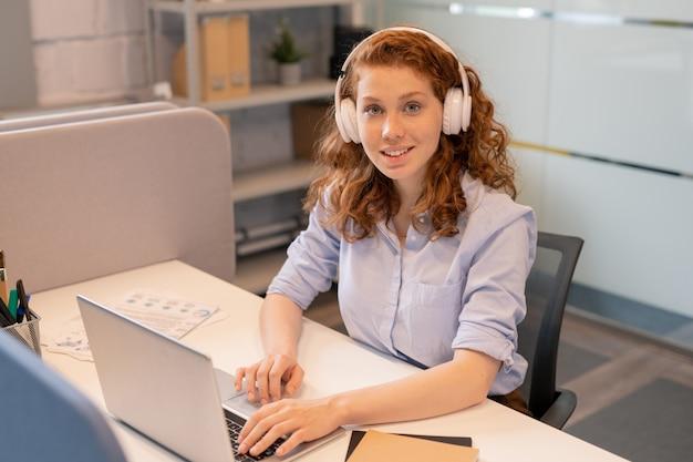 Портрет улыбающейся красивой рыжей леди-менеджера в беспроводных наушниках, сидящей за столом в коворкинге и отвечающей на электронную почту на ноутбуке