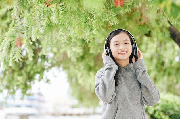 公園で一日を過ごすときにヘッドフォンで音楽を聴いて笑顔のかわいいベトナムの女の子の肖像画