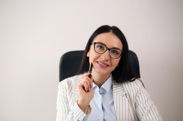 직장에 앉아 안경에 웃는 꽤 젊은 비즈니스 여자의 초상화.