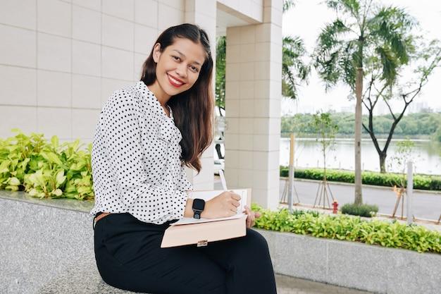 Портрет улыбающейся довольно молодой женщины-предпринимателя, записывающей идеи в планировщике