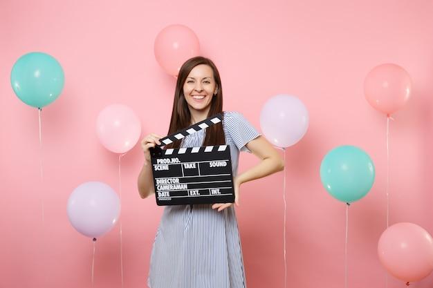 화려한 공기 풍선이 있는 분홍색 배경에 고전적인 검은색 필름을 만드는 클래퍼보드를 들고 파란 드레스를 입고 웃고 있는 예쁜 젊은 여성의 초상화. 생일 휴가 파티, 사람들은 진심 어린 감정.
