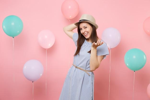 화려한 공기 풍선과 함께 파스텔 핑크 배경에 서 있는 밀짚 여름 모자와 파란색 드레스를 입고 웃는 예쁜 젊은 여성의 초상화. 생일 휴일 파티 사람들은 진심 어린 감정 개념입니다.