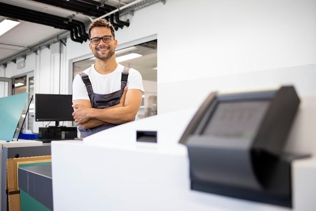 인쇄소에서 기계를 접시에 대고 컴퓨터 옆에 서 있는 웃고 있는 인쇄 작업자의 초상화.