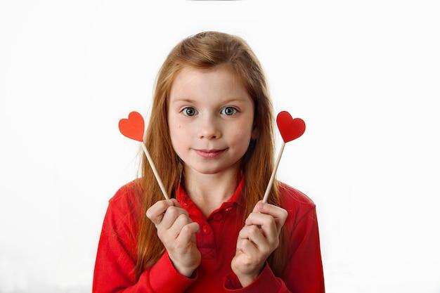 Портрет улыбающейся рыжеволосой кавказской маленькой девочки, держащей в руках красные сердца на палочках. любовь, день святого валентина, день матери, день отцов или концепция с днем рождения.