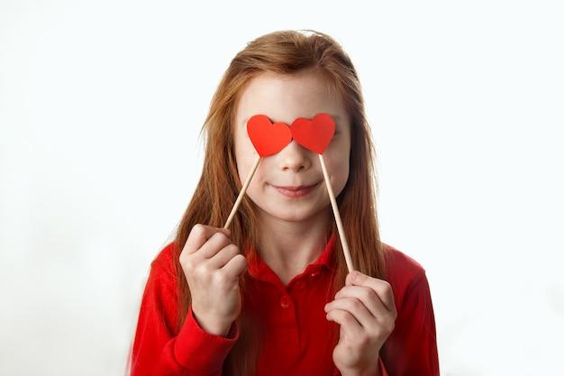 Портрет улыбающейся рыжеволосой маленькой девочки, закрывающей глаза красными сердечками на палочках.