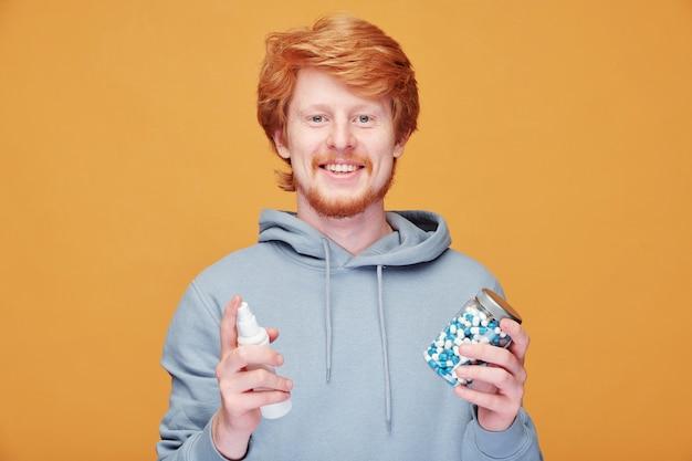 オレンジ色のコロナウイルスの概念にビタミンと手指消毒剤の缶を保持しているひげを持つ笑顔の赤毛の男の肖像画