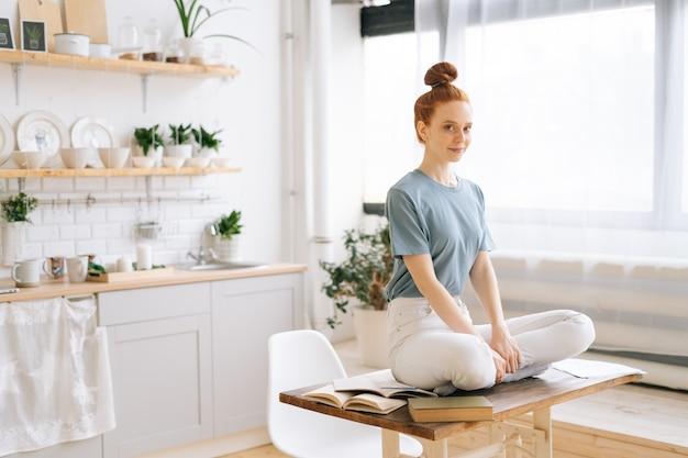 ホームオフィスの机の上に座って瞑想している笑顔の赤毛の若い女性の肖像画
