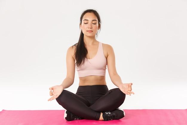Портрет улыбающейся, расслабленной азиатской фитнес-девушки, спортсменки в спортивной одежде, сидящей на резиновом коврике в позе лотоса с закрытыми глазами, медитации, практики йоги, снятия стресса, утренней гимнастики.