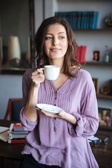 Портрет улыбающегося расслабленной зрелой женщины, держащей чашку кофе