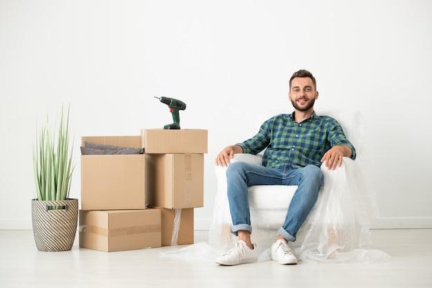移動ボックスのある新しい家でナプキンで覆われた肘掛け椅子に座ってリラックスした若いひげを生やした男の笑顔の肖像画