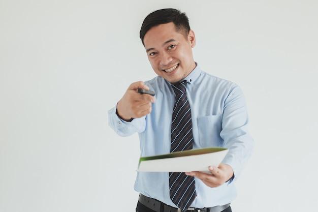 カメラでサインのためのペンと同意書を保持しながら青いシャツとネクタイを伸ばして手を着て笑顔のセールスマンの肖像