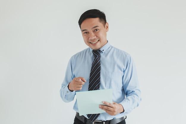 青いシャツとネクタイを身に着けている笑顔のセールスマンの肖像画は、カメラで白紙を指しています