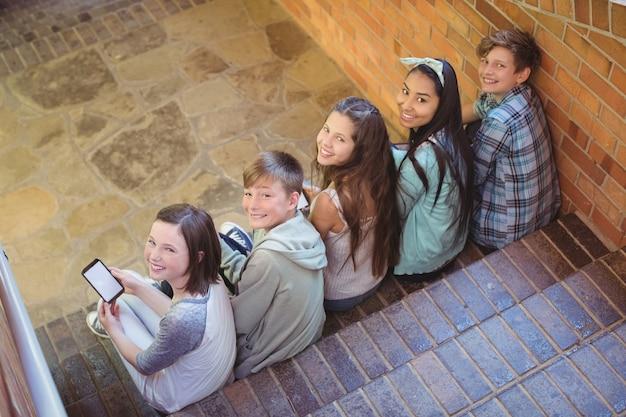 携帯電話を使用して階段に座っている学校の友達を笑顔の肖像画