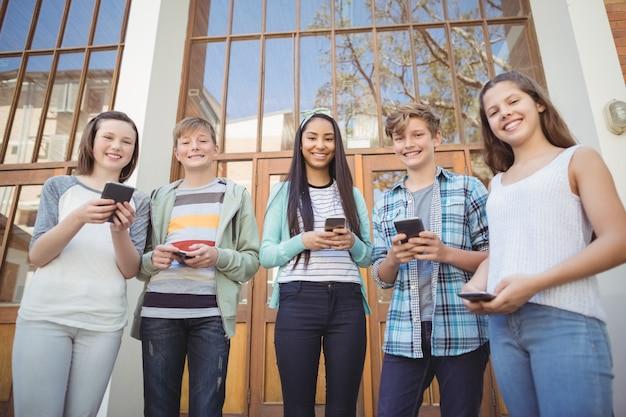 キャンパスで携帯電話を使用して学校の友達を笑顔の肖像画