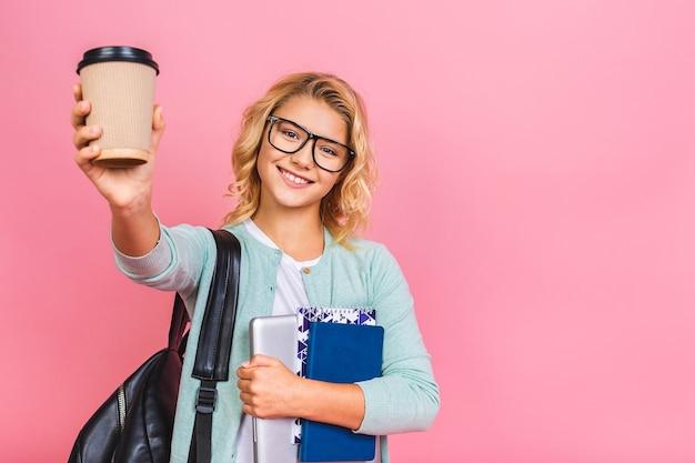 ランドセル、ラップトップと本、教育の概念を持つ笑顔の女子高生の子供の肖像画。